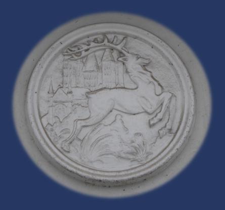 Doornik - Hert-Hart-Liefde - medaillon in een gevel bij de Schelde. Op de achtergrond de Onze-Lieve-Vrouwekathedraal met Rosace.