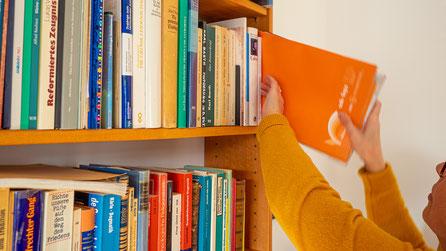 Bärbel Husmann nimmt ein Buch aus einem Bücherregal