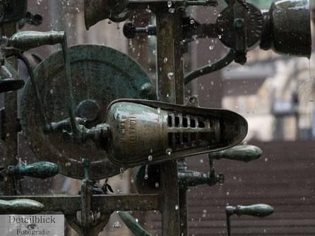 """Ausschnitt eines Springbrunnens mit einer Skulptur von """"Il Gocciolatoio"""" Daniel Spoerri. Aufnahme in einer kurzen Belichtungszeit."""