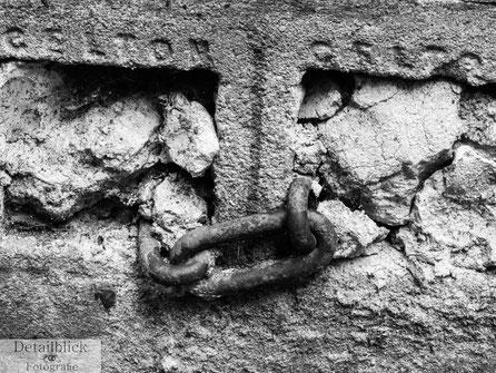 Gegenständliche Fotografie von einer eingemauerten Kette im Bremer Schnoor