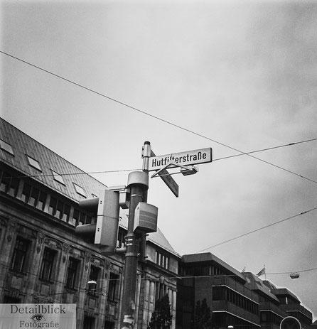 Gegenständliche Fotografie auf Detailblick Fotografie - Straßennamensschild mit ungewöhnlichem Anhängsel