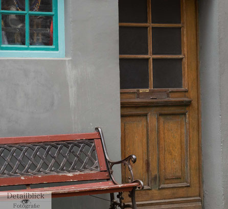 besondere farbliche Komposition von einer braunen Tür, roten Bank und eines türkisen Fensters.