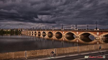 Pont de pierre, quais de Bordeaux sous un ciel lourd et gris, malgré un rayon de soleil. Photographie : Christian Coulais