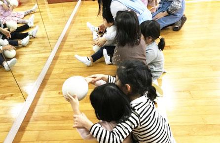 幼児教室の幼稚園児クラスのリトミックでボールのつき方について、年長児が年中・年少児にアドバイスをしています。
