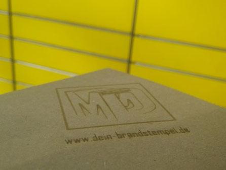 Branding mit Brennstempel auf Pappe
