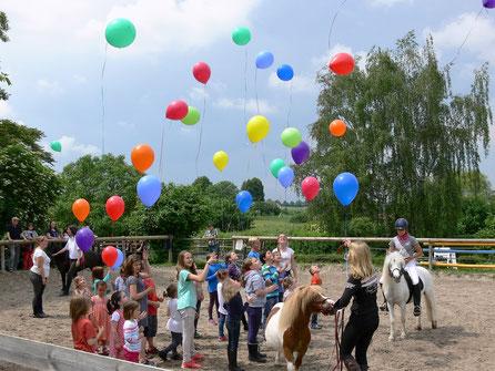 Alle Kinder lassen mit den Ponys Lufballons steigen