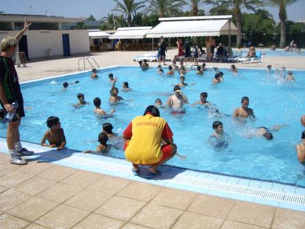 Monitores y socorristas vigilan a los niños en la piscina