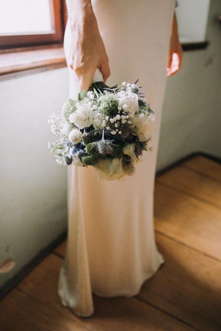 In der Hand hält die Braut einen Brautstrauß in weiß und blau, dazu trägt sie ein Brautkleid aus Satin, eng anliegend.