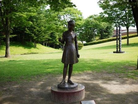 木々に囲まれた少女の像