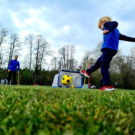 Ein Junge schießt einen Ball zum Trainer
