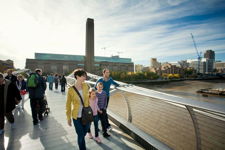 Family walking across Millennium bridge with Tate Modern in background, London, England, UK