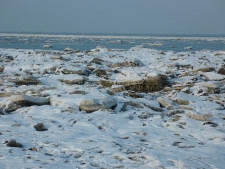 Die Flut spült immer neue Eisschollen an das strandnahe Watt, die sich zu dicken Packeisschichten stapeln.