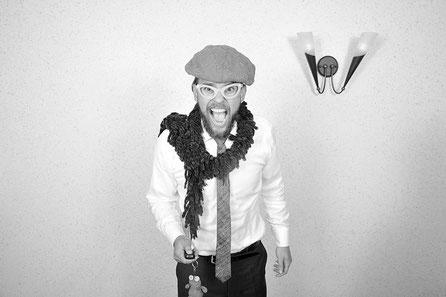 Ein Mann, verkleidet mit einer Mütze, einem Schal und einer Brille die in die Fünfziger Jahre passen würde schaut mit weit aufgerissenen Augen und drückt den Auslöse-Knopf des Fernauslösers der Photo-Box und macht das Foto was hier beschrieben wird.