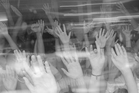 Feiernde Menschen die ihre Hände in die Höhe strecken, von der Lichtanlage sind Lichtspuren auf dem Bild zu sehen.