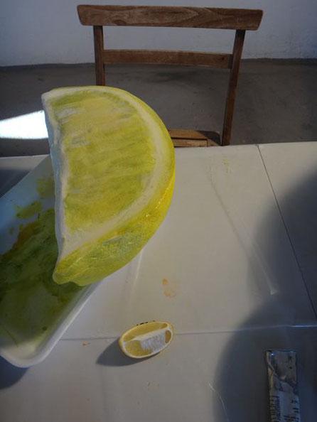 Reproducción de gajo de limón escala gigante (delante se ve el limón real) para el escaparate de una coctelería