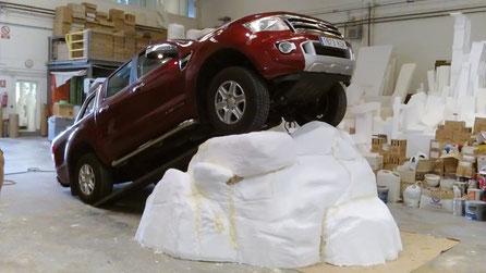 Volumen de roca, preparado con rampa auxiliar para subir un pesado todoterreno, en esposición concesionario.