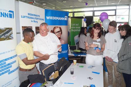 Thomas Lalla von der Wiedermann GmbH (2. von links) erklärt jungen Leuten bei einer Messe in Burg, worauf es bei der Ausbildung ankommt. Foto: Alpha-Report