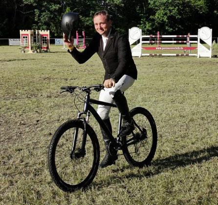 Tino Bode dreht auf dem Turnierplatz eine Runde mit neuem Fahrrad, der Ehrenpreis für seinen Sieg beim S*-Springen in Königsborn. Foto: Maria Kühne