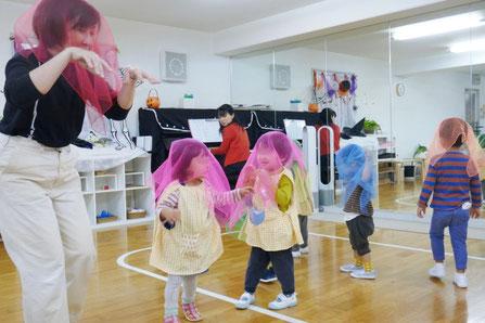 幼児教室のリトミックで、フィオーレコース(2歳児母子分)のお友だちがスカーフをかぶり、ピアノにあわせて体をゆらしています。
