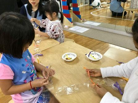 幼児教室のモンテッソーリの個別活動で幼稚園児がリボンを使ったキャンディ・レイの制作を集中して行っています。