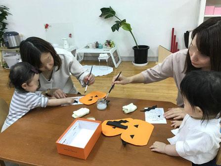 幼児教室のモンテッソーリの個別活動でピッコロコース(0歳児)のお友だちがかぼちゃのバッグをお母さまといっしょに制作しています。