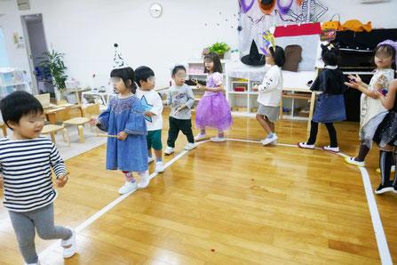幼児教室の幼稚園児クラス。ハロウィンにちなんだリトミックで、ピアノに合わせてスティックやカスタネットを鳴らして練り歩いています。