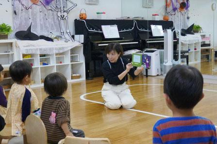 幼児教室のハロウィンでフィオーレコース(2歳児母子分離)の生徒がハロウィンの絵本を集中して聞いています。