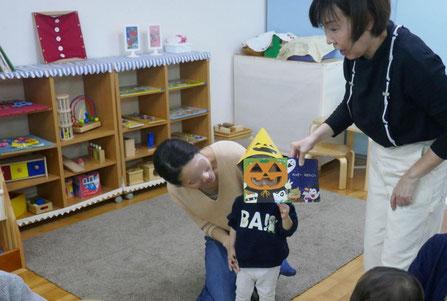 幼児教室のリトミックでステッラコース(1歳児)の生徒が、絵本についているお面をかぶってかぼちゃに変身しました。