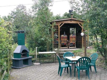 Auf der Terrasse lässt es sich gemütlich verweilen. Selbst bei regnerischem Wetter hat man einen trockenen Platz in der schönen Grillhütte.