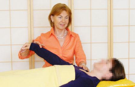 Heilpraktikerin und Kinesiologin Ortrud Hannemann beim Ausführen des Mukeltests. Der Patient liegt dabei in bequemer Ruhelage zugedeckt  auf dem Rücken