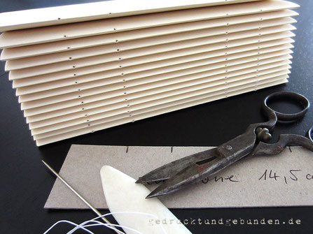 Bedrucktes elfenbeinfarbenes Papier gefalzt ineinandergesteckt und vorgestochen - Papierlagen zur Weiterverarbeitung zum fadengehefteten Buchblock.