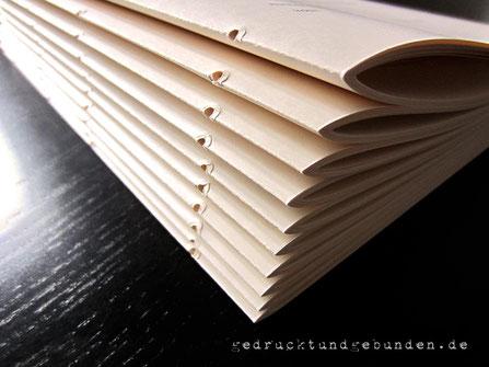 Bedruckter elfenbeinfarbener Fotokarton gefalzt ineinandergesteckt gelocht = Papierlagen zur Weiterverarbeitung mit Leder. Ziel: Lederbuch Softcover Kreuzstichbindung
