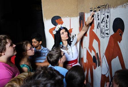 Daniela Rutica erklärt einer Kinder-Gruppe die Bedeutung der Hieroglyphen.