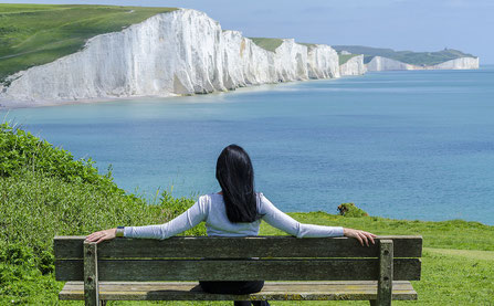 Entspannte Frau auf Holzbank blickt auf das Meer und weiße Klippen
