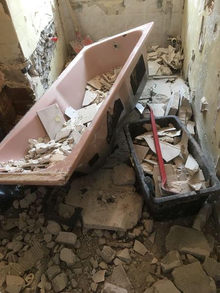 Ausbruch oder Abbruch von einem alten Badezimmer , Fliesen abgeschlagen , Schutt , rosa Badewanne , MADEJA-DIE HAUSGESTALTER