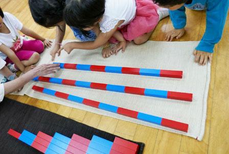 幼稚園児クラスのモンテッソーリ活動で、計算棒を使ったグループ活動を行い、算数の基礎を育んでいます。