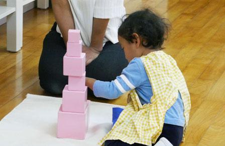 感覚教具のピンクタワーを使った活動を行い、順序づけの感覚を育んでいます。