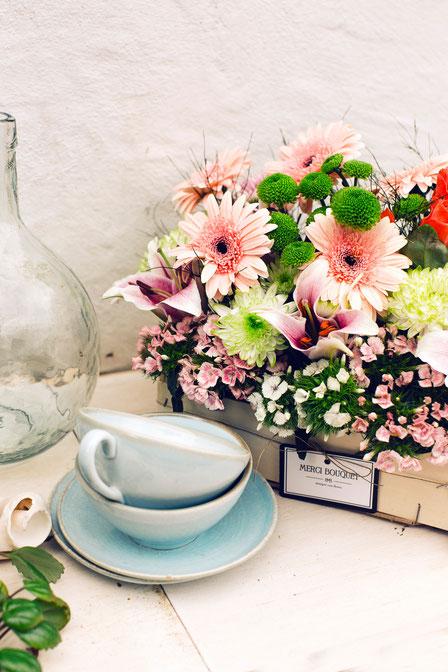 Caja de madera repleta de flor de temporada