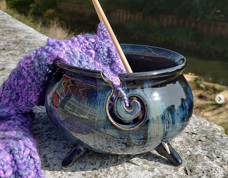 Purple/blue/green ceramic yarn bowl with bamboo knitting needles and purple chunky knitting yarn.