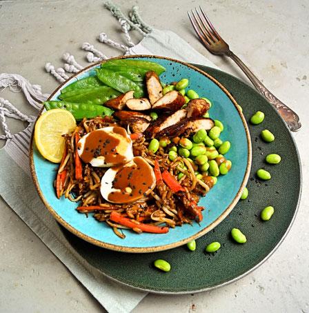 Bowl mit gewürztem Hähnchenfleisch, gebratenem Reis, Edamame, Zuckerschoten und Ei mit Erdnußsauce