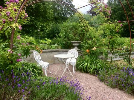 Zwei verschnörkelte, alte Stühle stehen inmitten der Blumen des Rosengartens und laden zum Verweilen ein.