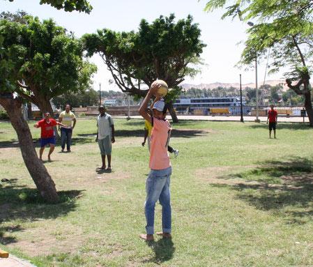Teenager bei einem Fußballspiel in einem Park in Assuan und einem Nilkreuzfahrtsschiff im Hintergrund.