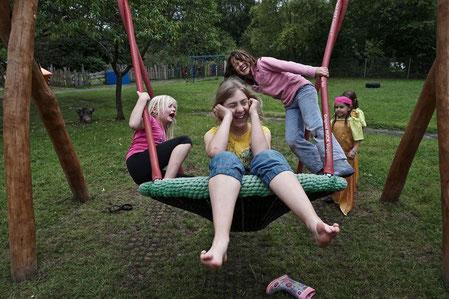 Drei Mädchen schwingen auf einer Schaukel und lachen dabei. Im Hintergrund stehen weitere Mädchen. Sie befinden sich auf einem Spielplatz.