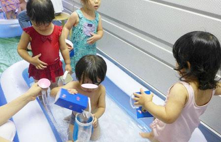 フィオーレコース(2歳児)のお友達が、プールの中でぞうさんじょうごやミニバケツを使って、みんなで水遊びを楽しんでいます。