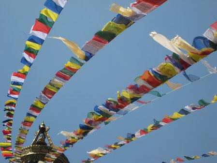 Buddhistische Gebetsfahnen im Wind vor blauem Himmel