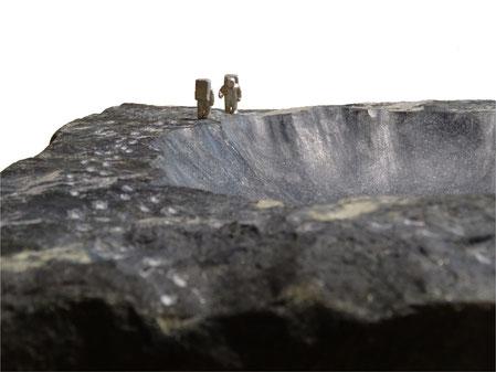 Mondkrater als Schale aus Stein. Mondlandung. Erste Mondlandung. Zum 50. Jahrestag der ersten Mondlandung, eine künstlerische Darstellung aus schwarzem Stein. Die Astronauten bestehen aus Silber.