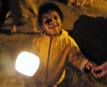 7-Petits et grands chantent la Vierge Marie, le visage illuminé par le flambeau