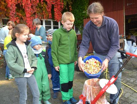 Reimar Voß  befüllt die Saftpresse mit kleinen Apfelstücken.