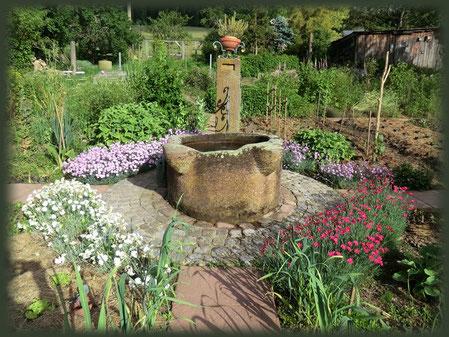 Mittelpunkt und Lebensquell im Bauerngarten ist der Sandsteinbrunnen.