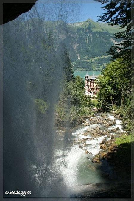 Hinter dem Wasserfall durchspaziert mit Blick auf das Hotel Giessbach und den Brienzersee.